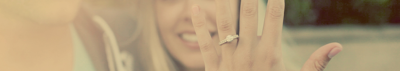 A close up photograph of a woman holding up a luxurious diamond wedding ring.