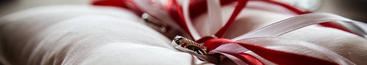 A close up photograph of an elaborate diamond wedding ring, on a luxurious red fabric.